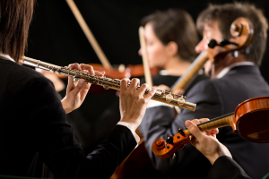 Professional female flutist in concert with symphony orchestra players on background.