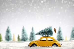 Miniature yellow car with fir tree on snow